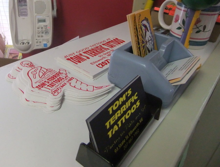 A variety of promotional materials are available on the counter at Tom's Terrific Tattoos. A side effect of making your business name fun: people will want to promote it.