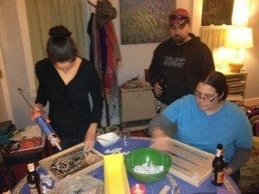 The group tackles mosaicing. Hope handles the silicone, Sam lays out her pattern, and Nate looks on in interest.