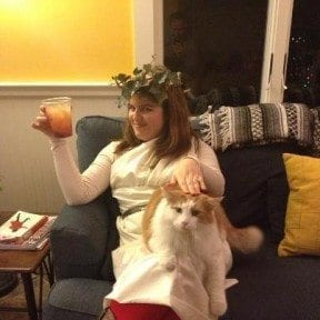 Me in my toga, awaiting partygoers. I picked the picture where the cat looks most annoyed. Yes, that is real ivy on my head.